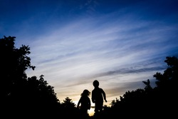 Two brothers run together through a field between trees, at sunset in silhouette.