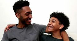 Two brothers together smiling. Black mixed race siblings, older and younger brother