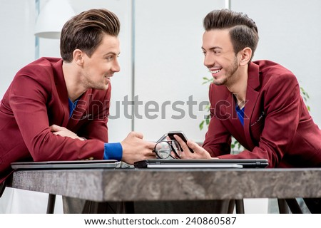 Two brothers twins in red jackets discussing something with smart phones at the office table