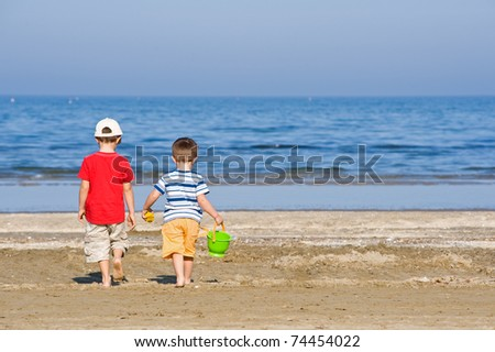 Two brothers walk along the beach in a sunny day.