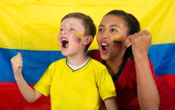 Two brothers with the flag are watching a game and totally excited.