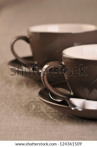 Two brown coffee cups with sugar cubes