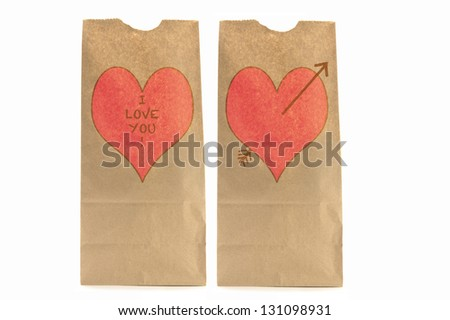 Two Brown paper lunch bags with heart and I love you written on it the other with Cupid's arrow
