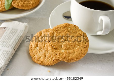 Two brown wholemeal biscuits with a white cup and saucer