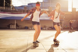 Two Brunette teenage girls friends in hipster outfit (jeans shorts, gumshoes, plaid shirt, hat) with a skateboard at the park outdoors. Copy space