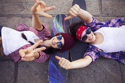 Two Brunette teenage girls friends in hipster outfit (jeans shorts, gumshoes, plaid shirt, hat) with a skateboard at the park outdoors.