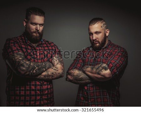 Two brutal mans with beards and tattoo isolated on grey background. Crosed arms. Stock photo ©