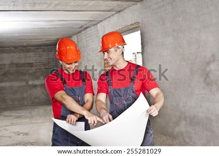 two builder engineer Architects working in empty concrete room  - planning and looking at blueprint hold in hands  Builder wear blue uniform and red hardhat shirt overall Man show in paper plan