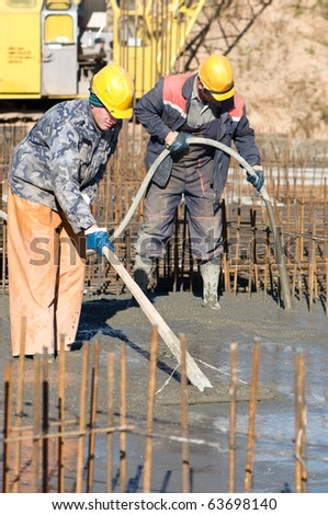 two builder workers during concrete works at construction site. Leveling and vibration