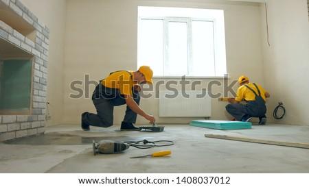 Two builders in uniform repairing apartment indoor. Builder processing concrete. Workers renovating home. #1408037012