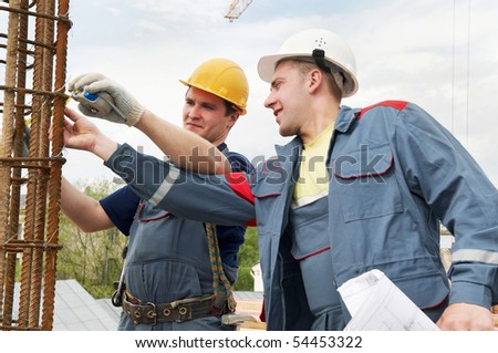 two builders workers checking with measure tape reinforcement column
