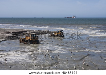 two Bulldozers on the beach on a dredging project in holland with dredger in background