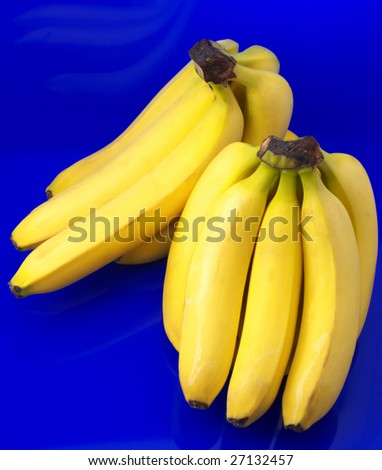 Two bunch of bananas on blue background.