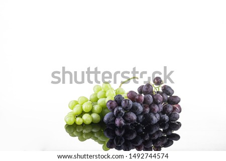 Two bunches of green and black grapes on a white background