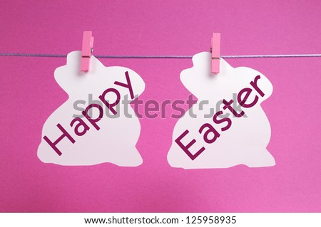 Two bunny rabbit shape Easter cards hanging from a line, with Happy Easter message in pink..