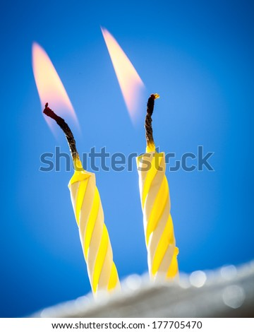 Two burning birthday candles over blue background