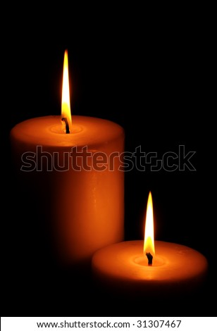 Two burning candles against dark background
