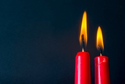 Two burning candles of red color on a black background. The image has a blank space for your text.