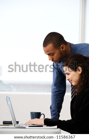 two business associates with a grey laptop