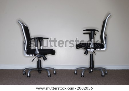 Two business chairs where one chair is looking at the other when which is taller