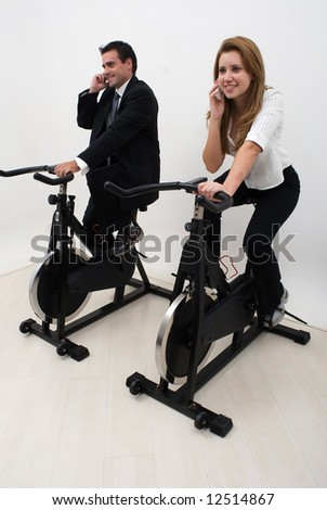 Two business colleagues riding exercise bikes and chatting on their cell phones. Isolated.