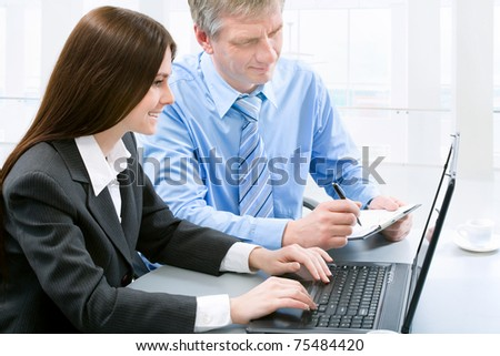 Two business colleagues sitting around table and working together.