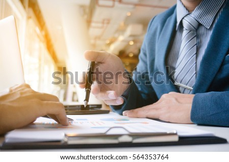 two Business Executives at desk discussing sales performance in a office.