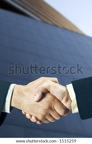 Two business man shaking hands in front of a modern building, nice light and depth of field. - stock photo