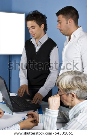 Two business man using laptop at a meeting and other  people have an conversation