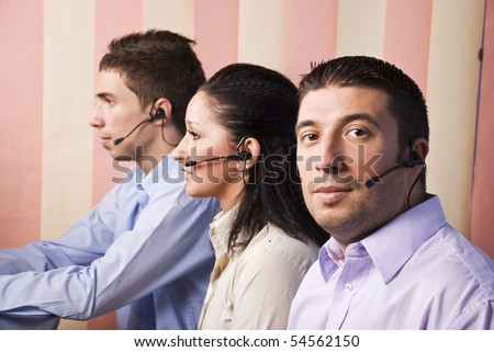 Two business men and one businesswoman  customer service working in office,focus on first man that looking at ypo
