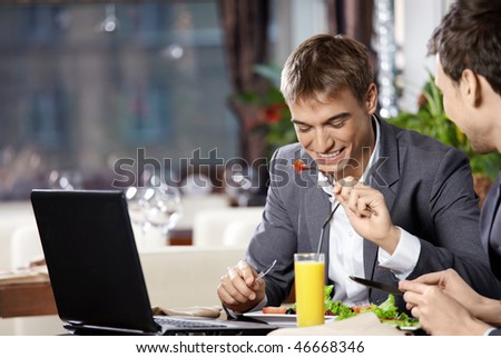 Two business men have dinner at restaurant - stock photo