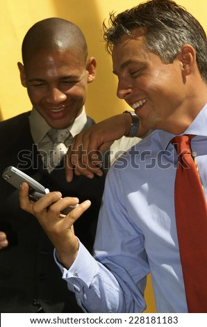 Two business men looking at handy