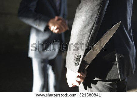 two business men making a deal but hiding knives