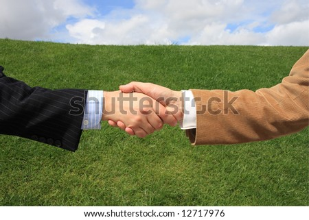 Two business men making a deal with a handshake at the field