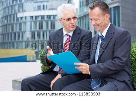 Two business men partner talking about a file