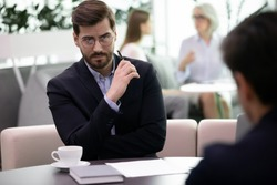 Two business men partners during meeting in office. Negative attitude to applicant, bad first impression, hr manager looking at candidature with distrust, unsuccessful, failed job interview concept