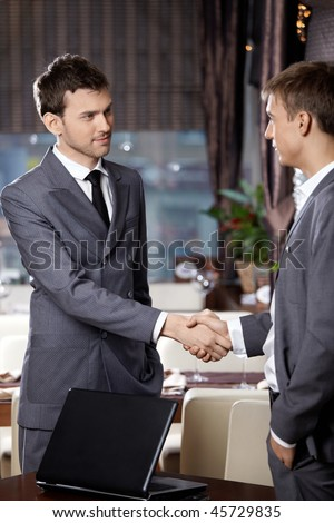 Two business men shake hands each other at a meeting at restaurant