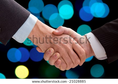 Two business men shaking hands on a background of color light