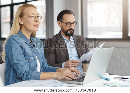 Two business partenrs of colleagues do paperwork, review finances and study financial documents, have clever expressions. Corporate associates develop new project, work in office. Cooperation #753349810