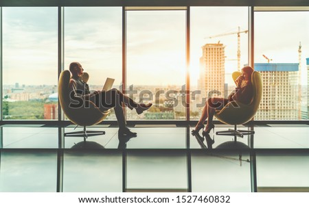 Two business partners: a man entrepreneur with a laptop and his female colleague with a paper cup with a coffee are sitting on curved armchairs in front of each other with a construction site behind #1527460832