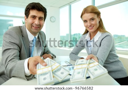 Two business partners at workplace giving money and looking at you