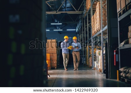 Two business partners in formal wear and with protective yellow helmets on heads walking and talking about business. Younger one holding folder with data while older one using tablet. Stockfoto ©