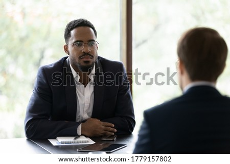 Two business partners meet in office solve current issues. Caucasian applicant rear view answer questions while African serious hr manager listen him feels sceptic. Negotiations, job interview concept
