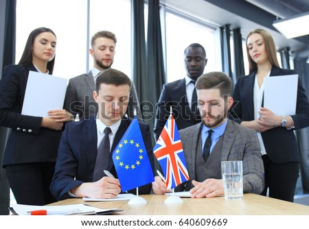Two business partners signing a document. The European Union and Great britian. Brexit