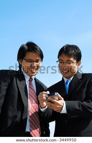 Two business partners working together looking at a PDA