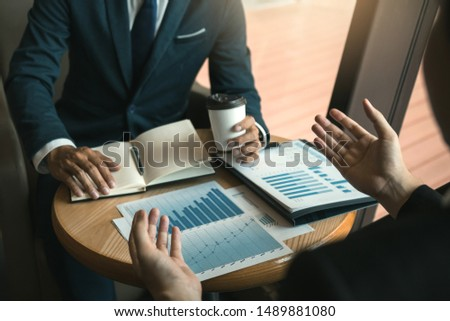 Two business partnership coworkers analysis cost work progress and gesturing with discussing a financial planning graph and company financial during a budget meeting in office room. #1489881080