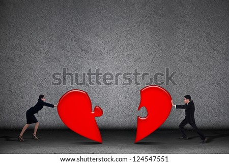 Two business people are putting love puzzle together on grey background