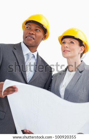 Two business people are wearing hard hats and holding a paper