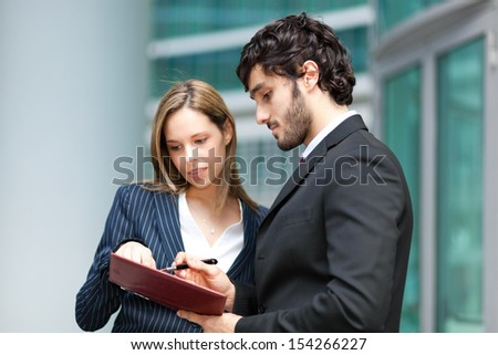 Two business people consulting an agenda