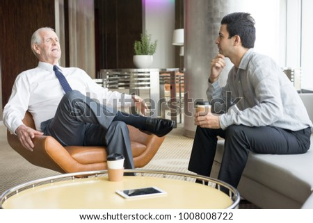 Two Business People Conversing in Office Lounge #1008008722
